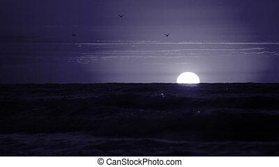 White moon on the horizon above the sea.