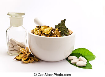 White mortar and pestle. Herbals, pills and green leaves.