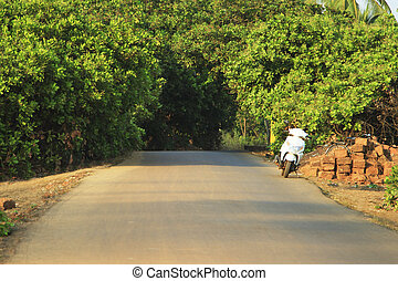 White motor bike on empty road in GOA