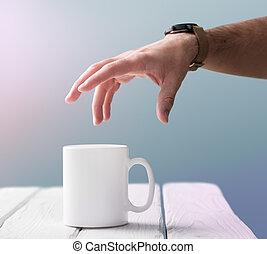 White mug mockup - Man's hand is going to take a blank white...