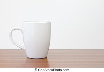 White mug on dark wooden table with white wall