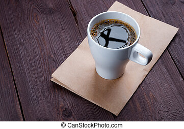White mug with coffee on a wooden table.