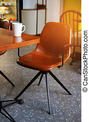 White mug with coffee or tea on a wooden table in the cafe. There's a leather chair next to it. Stylish design, vintage style. Breakfast or coffee break in the afternoon or evening. Coffee addiction.