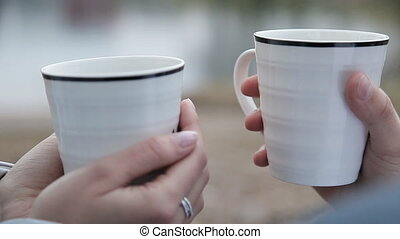 White mugs with hot tea in their hands - Young couple...