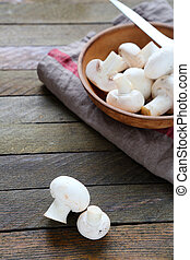 white mushrooms in a bowl and knife