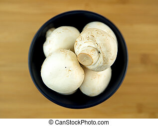 White mushrooms in black bowl on wooden board