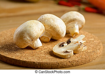 White mushrooms on the wooden background
