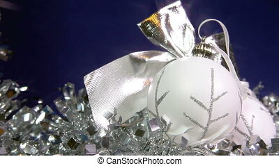 white New Year's balls and tinsel on a blue background,