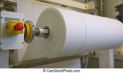 White non-woven material with nanofiber is wound on a spool ...