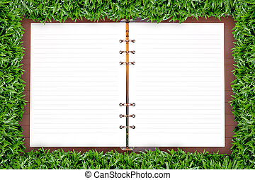 White notebook in green grass framing