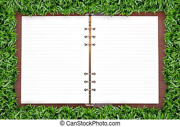 White notebook in green grass framing