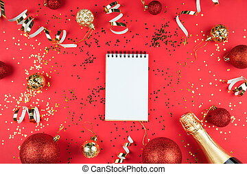 White notebook sheet on a bright red background with gold sequins, balloons, streamers and champagne