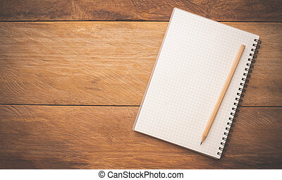 White notebooks and pencil laying on a wooden table