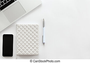 White office desk with a part of laptop, mobile phone, pen