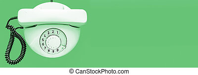 White old telephone with rotary dial on green background. Flat lay. Top view. Banner. Place for text