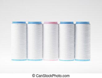 White on white, spools of thread on white background