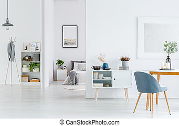 White open space interior - Grey chair at wooden table in...