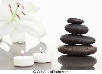 White orchid with lighted white candles and a black pebbles stack