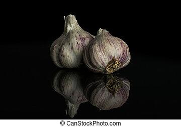 White organic garlic isolated on black glass