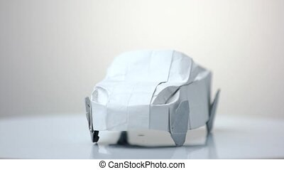 White origami car model. Automobile figurine made of folded...
