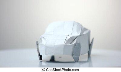 White origami car model. Automobile figurine made of folded...