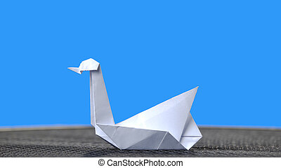 White origami swan on blue background.