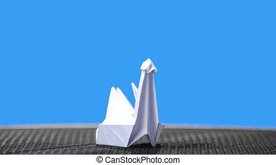White origami swan on blue background. White paper crane on...