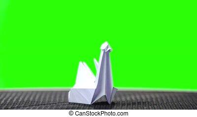 White origami swan on green screen. Folded paper bird on...