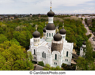 White orthodox church among green trees with dome under reconstruction aerial view. St. John the Forerunner