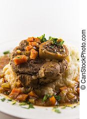 Osso buco meal with sauce, mashed potato and carrot vegetable. White background and very shallow depth of field.