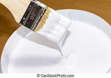 White paint flowing down from the brush into a bucket with paint