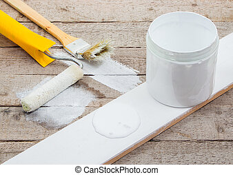 White paint with a brush or roller for painting wooden planks