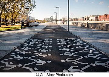 White painted pedestrian crossing sign on asphalt
