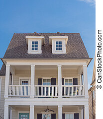 White painted porch with banister and dormer roof of two story houses near Dallas, Texas