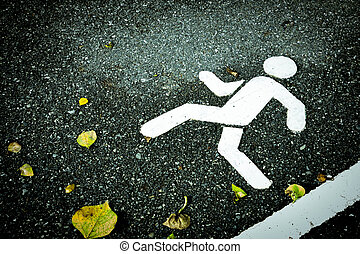 White painted sign on asphalt. Pedestrian lane and yellow dry leaves. Skip over obstacles.
