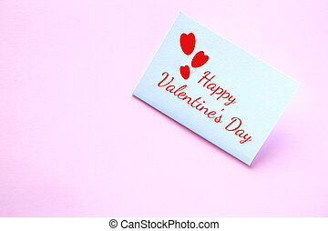 White paper card with the inscription Happy Valentine's Day on a pink background