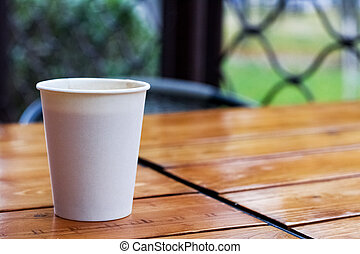 White paper cup with coffee on a wooden table