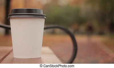 White paper cup with hot drink in autumn city park close up with shot defocused background skater boy picks up the paper cup