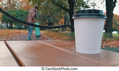 White paper cup with hot drink on the bench in autumn city park close up with background skater boy walking people