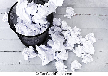 White paper in the trash can - Recycle. Crumpled paper in...