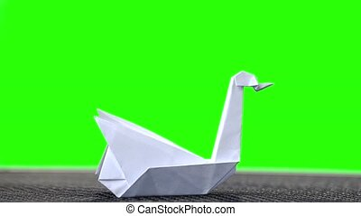 White paper origami swan. Green hromakey background for...