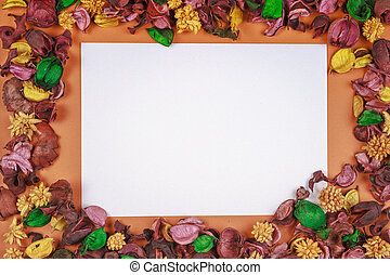White paper piece surrounded by colorful dried flowers and leaves frame. Top view, flat lay. Copy space for text