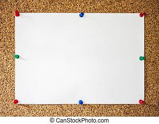 White paper pinned on cork board