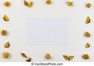 White paper sheet surrounded by yellow dried flowers, plants border frame on white background. Top view, flat lay.