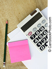white paper with calculator pencil and memo  on wood table