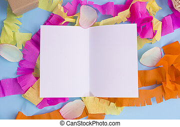 White paper with colorful ribbon on blue background.