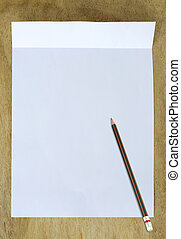 white paper with pencil on wooden table