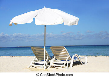 Single white parasol and sun lounger on deserted tropical beach