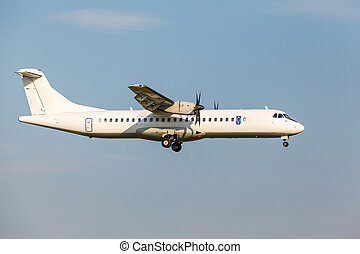 white passenger turboprop aircraft with the gear landing on...