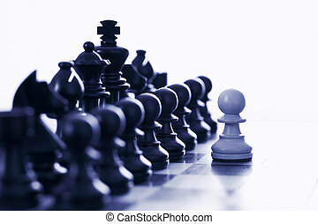 White pawn challenging black chess pieces